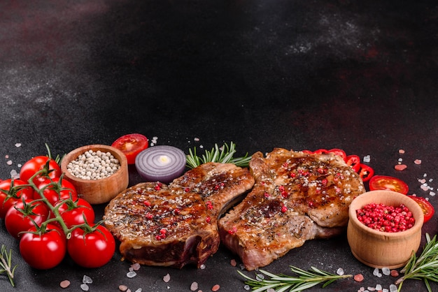 Fresh delicious juicy steak on the bones with vegetables and spices. pork juicy steak grill on dark table Premium Photo