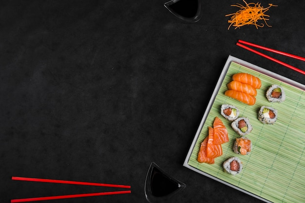 Fresh and delicious sushi japanese food with chopsticks on black background Free Photo
