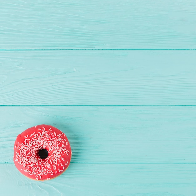Fresh donut with sprinkles on wooden table Free Photo