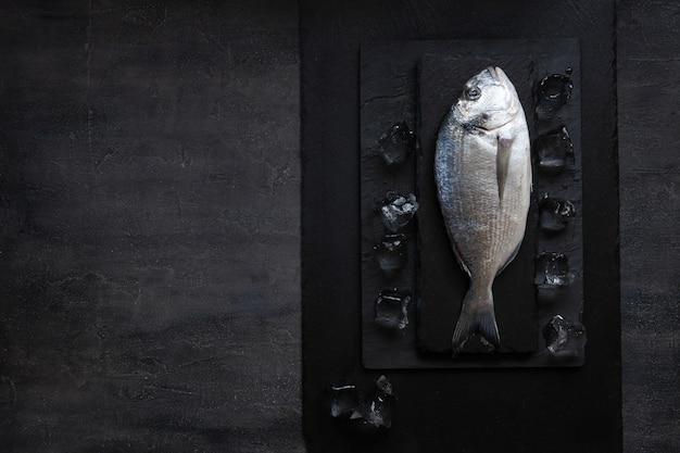 Fresh dorado fish with ice on stone cutting board on dark