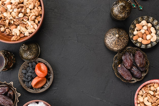 Fresh dried fruits; nuts and dates for ramadan on black backdrop Free Photo
