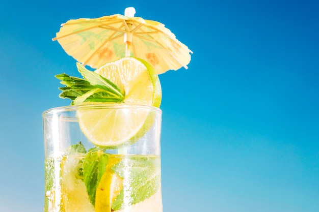 Fresh drink with sliced lime and mint in umbrella decorated glass Free Photo