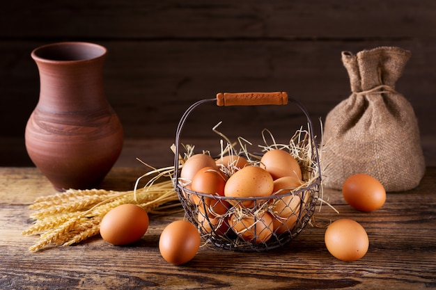 나무 테이블에 바구니에 신선한 계란 프리미엄 사진