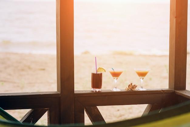 木製の端に新鮮なエキゾチックなカクテル。眼鏡の間に横たわるシェル。ストローとレモンのコーラ Premium写真