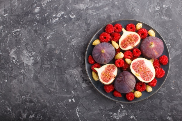 Fresh figs, strawberries and raspberries on blue plate on black concrete background Premium Photo