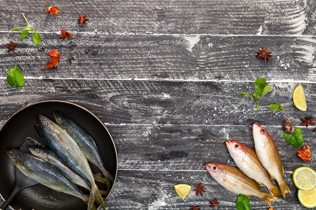Fresh fish in black frying pan, fish with spices and vegetables, cooking background concept Premium Photo