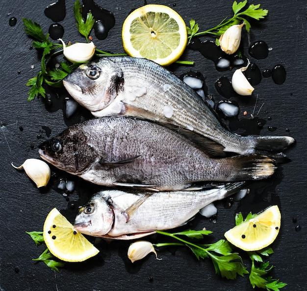 Fresh fish orata over a black stone with vegetables Premium Photo