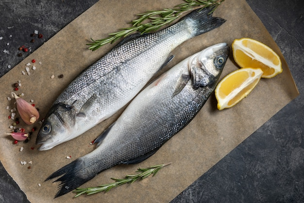 Fresh fish seabass and ingredients for cooking, lemon and rosemary. dark background top view. Premium Photo
