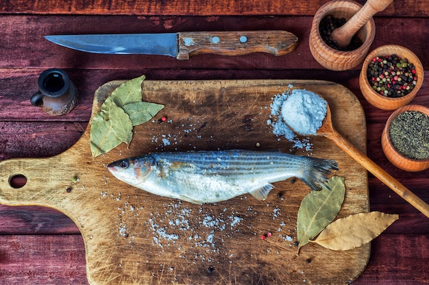 Fresh fish smelt for cooking on a kitchen board Premium Photo