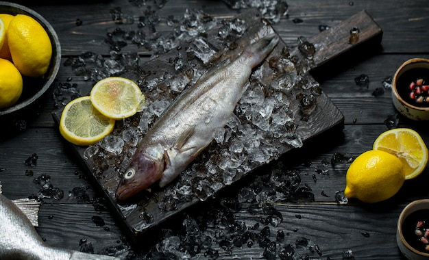 Fresh fish on a wooden board with ice cubes and lemon Free Photo