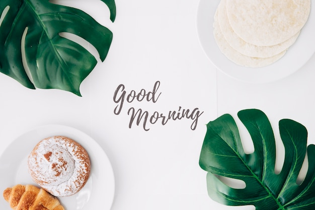 Fresh flour tortillas; baked bun; croissant breakfast with good morning text on paper and green monster leaves on white background Free Photo