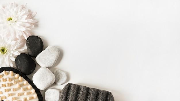 Свежий цветок; галька; пемза и массажная щетка на белом фоне с пространством для текста Бесплатные Фотографии