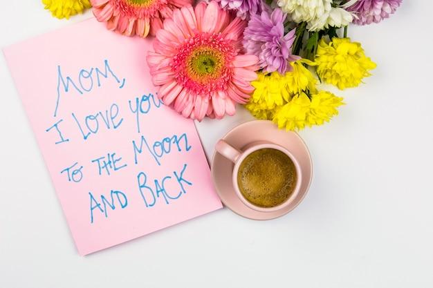 言葉と飲み物のカップと紙の近くの新鮮な花 無料写真