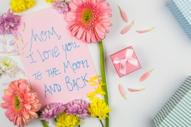 言葉、花びら、プレゼントボックスと紙の近くの新鮮な花 無料写真