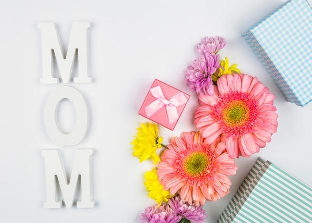 プレゼントボックスとママの単語の近くの新鮮な花 無料写真