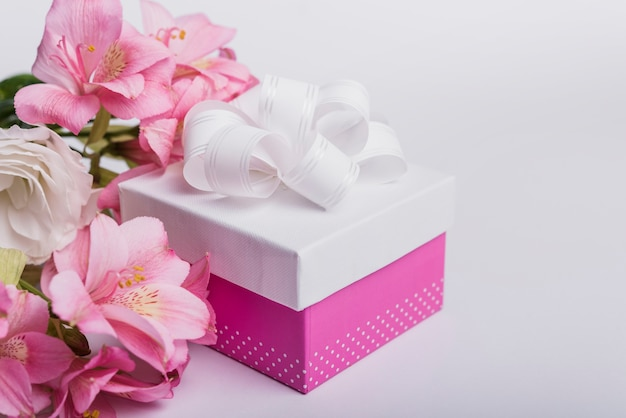 Fresh flowers and present box on white background Free Photo