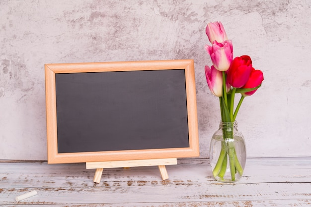Fresh flowers on stems in vase and chalkboard Free Photo