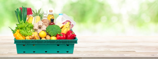 Fresh food and groceries in tray box on wood tabletop banner background Premium Photo