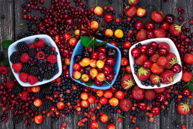 Fresh forest berries on wooden background Premium Photo
