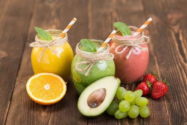 キッチンテーブルにスムージーと新鮮な果物と瓶 Premium写真