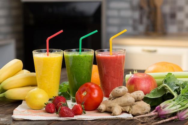 ガラスの台所のテーブルに新鮮な果物と野菜のスムージー Premium写真