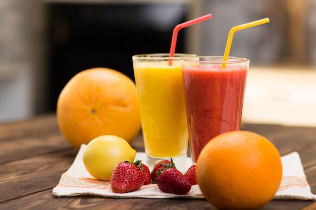 2つのガラスの台所のテーブルの上の新鮮なフルーツのスムージー Premium写真