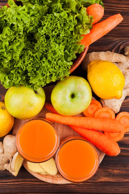 Fresh fruit and vegetables with juice on table Free Photo