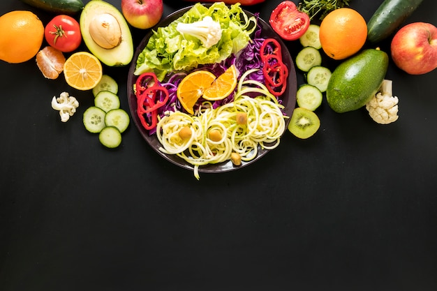 Fresh fruits and chopped vegetables against black backdrop Free Photo