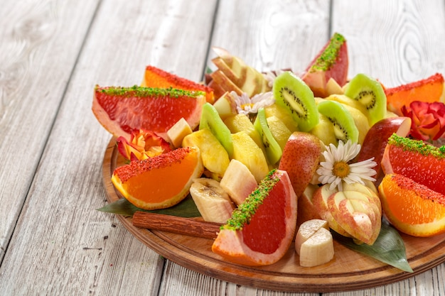 Fresh fruits in plate on wooden table Premium Photo