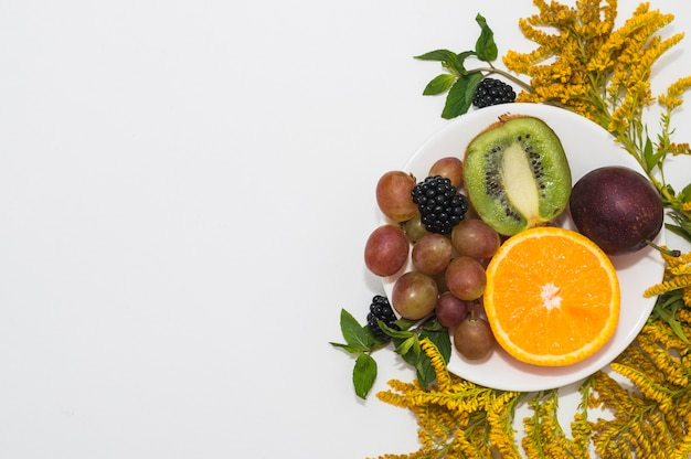 Fresh fruits on white plate with yellow flowers against white background Free Photo