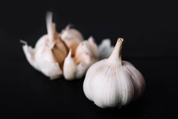 Fresh garlic bulb on black surface Free Photo