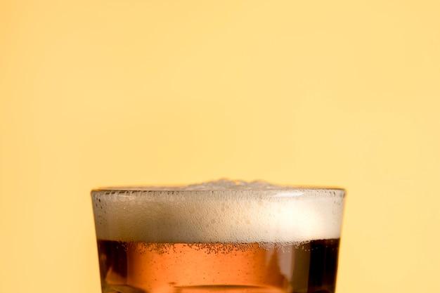 Fresh glass of beer on yellow background Premium Photo