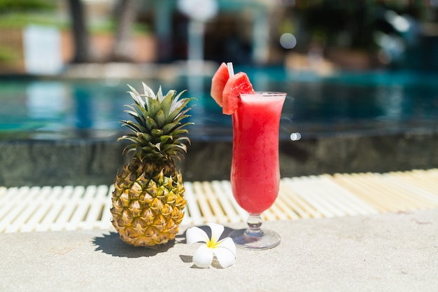Fresh glass of watermelon smoothie drink, pineapple and tropical plumeria flower standing n Premium Photo