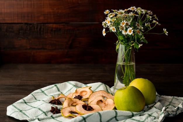 新鮮なおばあちゃんの鍛冶屋のリンゴ、庭の花、ドライフルーツ、スターアニスの壁に暗い木製のテーブルの市松模様のキッチンタオル Premium写真