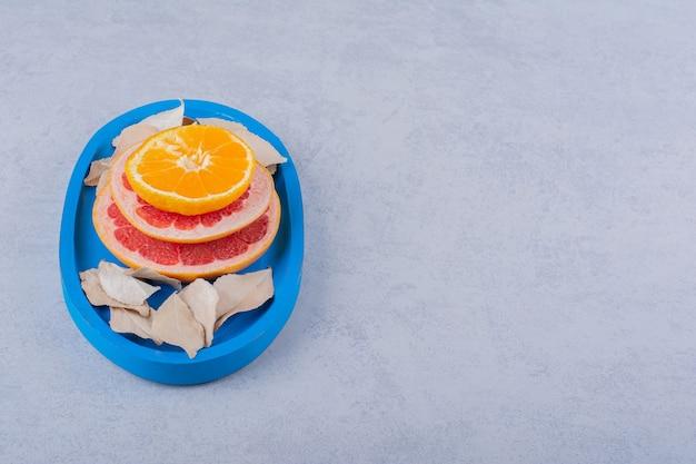 青いプレートに新鮮なグレープフルーツ、レモン、オレンジのリング。 無料写真