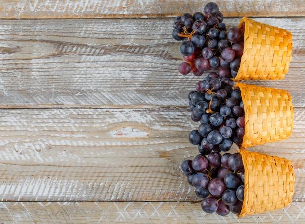 枝編み細工品バスケットの新鮮なブドウフラット木製の背景に置く 無料写真