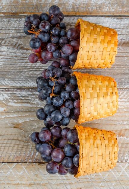 木製の背景に枝編み細工品バスケットの新鮮なブドウ。上面図。 無料写真