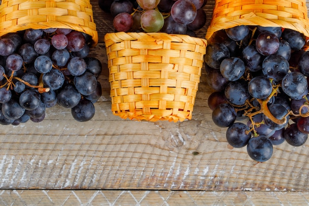 木製の背景に枝編み細工品バスケットの新鮮なブドウをクローズアップ。 無料写真
