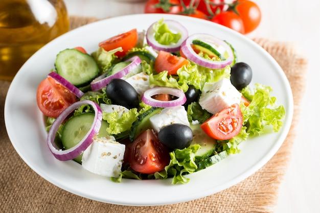 Fresh greek salad made of cherry tomato, ruccola, arugula, feta, olives, cucumbers, onion and spices. Premium Photo