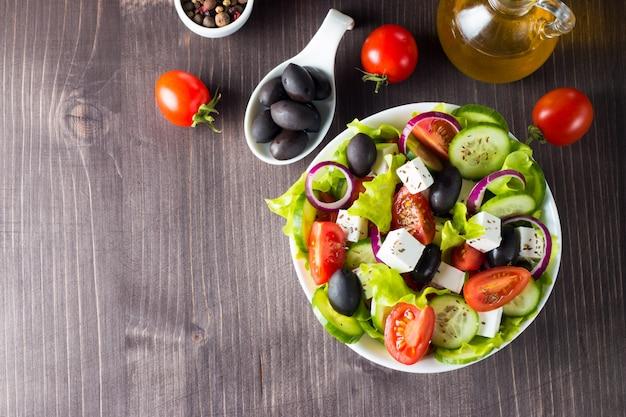 Fresh greek salad on wooden background. Premium Photo