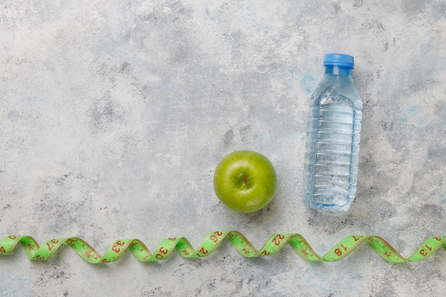 Fresh green apple, measure tape and bottle of fresh water on grey concrete Free Photo