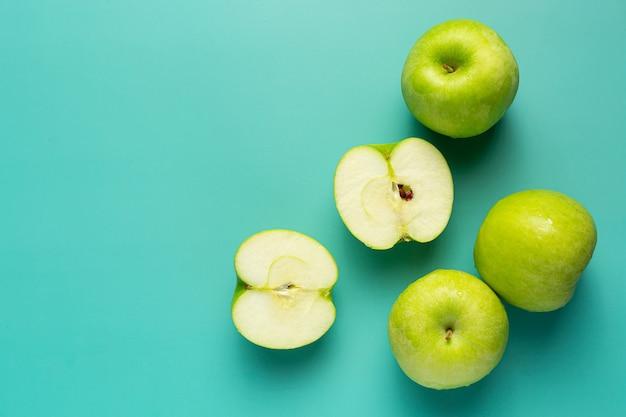 Свежие зеленые яблоки, разрезанные пополам, положить на светло-зеленый фон Бесплатные Фотографии