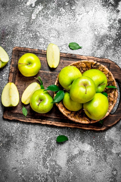 素朴なテーブルのまな板に新鮮な青リンゴ。 Premium写真