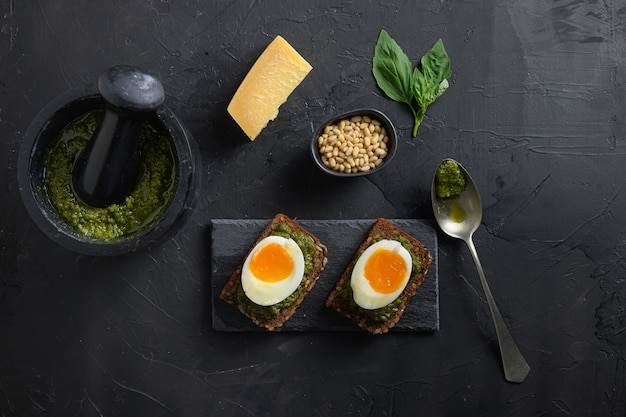 Песто из свежего зеленого базилика в ступке, домашнее на старых деревенских деревянных яйцах, хлеб панини с соусом песто Premium Фотографии