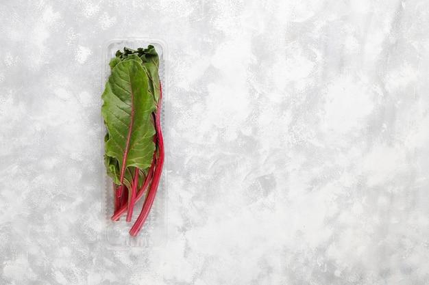 Fresh green beet leafs (mangold) in plastic box on grey concrete Free Photo