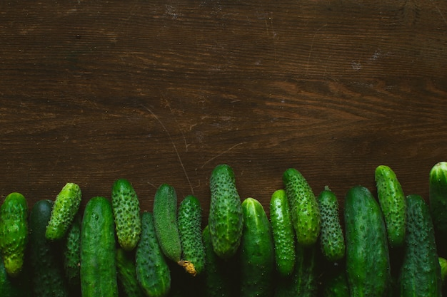 Fresh green cucumbers on wooden background Premium Photo