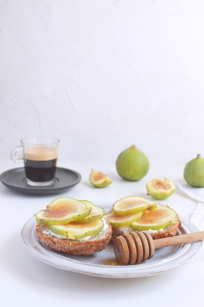 Fresh green figs sandwiches canapes grey rustic plate black coffee Premium Photo