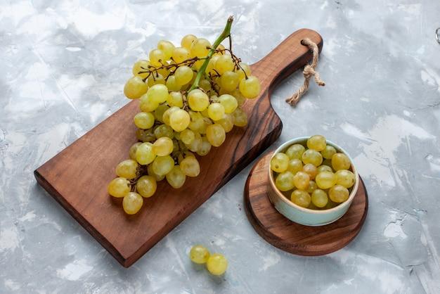 光の上の茶色の机と新鮮な緑のブドウ 無料写真