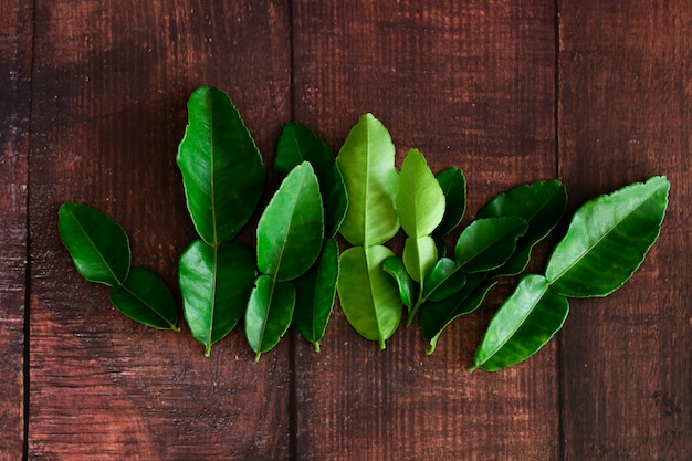 Fresh green kaffir lime leaves on wooden desk ,  asia's food Premium Photo