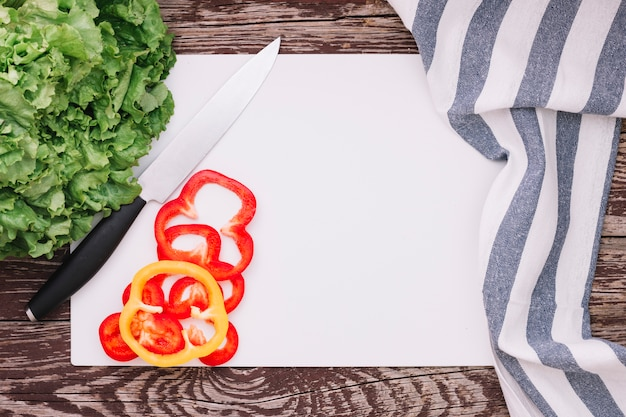 Fresh green lettuce and bell pepper on white paper with stripe napkin on wooden table Free Photo